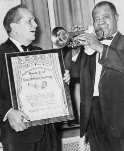 Louis Armstrong playing his trumpet while being presented with an award. Courtesy of Library of Congress Prints and Photographs Division.