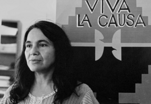 "Dolores Huerta standing in front of union flag that reads, ""Viva la Causa"" in the 1970s."