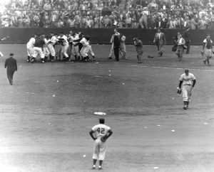 Players greet Thomson at home plate after he hits the game winning home run.