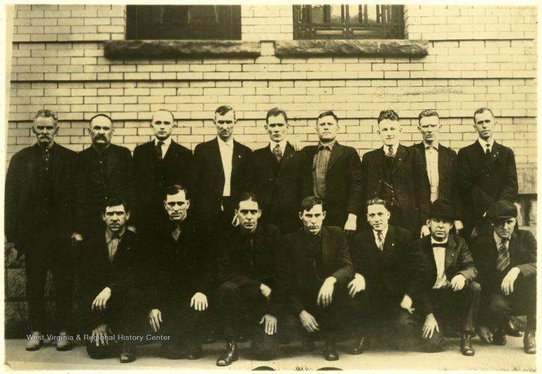 16 men in suits stand pose for a picture outside of a courthouse in a sepia photo.